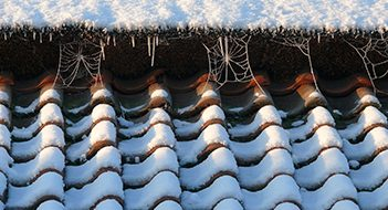 Winter with roof with snow and ice which can damage your roof and require attention from a roofing contractor Sheffield